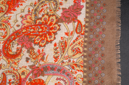 Texture, pattern, background. Silk fabric - paisley on a beige background. This beautiful silk border print has paisley and floral print in orange and grey on a natural colored background.