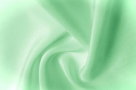 Texture background pattern. Green silk fabric. Closeup of a corrugated green silk fabric. Advertising space. Smooth elegant green silk can be used as a wedding background. Stock Photo