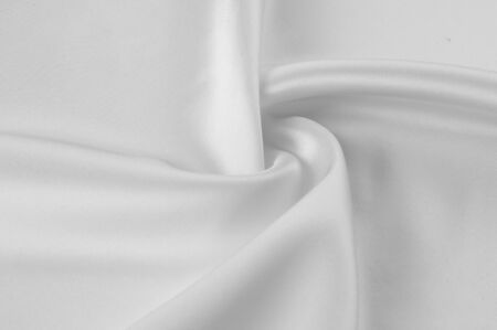 Texture, background, pattern. White silk fabric, Smooth elegant white silk or satin fabric fabric can be used as a wedding background. Luxury Christmas background or New Year background design Stock Photo