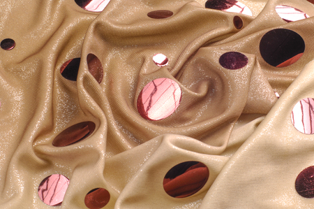 Background texture, drawing. Pink Mirror Pietz Lycra Fabric Last Piece. 2-strip tensile mass of lycra spandex. Beige background with big pink mirror glitter sequins.