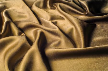 シルク生地の金属糸メタリック光沢ゴールド製の生地。ちょうど素晴らしい滝を見ているように、この金色の黄色の絹のシャルムーズは一人で立っ
