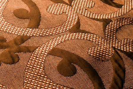 Texture, background, pattern. Fabric Tweed cotton golden-brown with a floral pattern