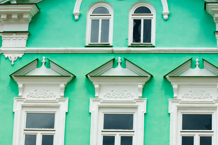 pilasters: Old city, Prettily suburban town. Architectural details and decoration of the vintage stucco facade framing the windows - console, protome, mascaron, capital, pilasters, wreaths, relief and other.