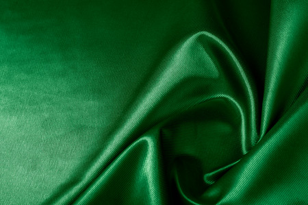 Texture, background, pattern. Texture of green silk fabric. Beautiful emerald green soft silk fabric.