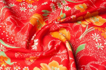 Texture, background, pattern. Cotton cloth of red color, On the fabric are painted flowers yellow white