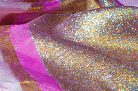 Texture, background, pattern. Combined silk white fabric and gold and silver damask fabric, pink ribbons Stock Photo