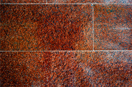 Texture, background, pattern. Photo of red granite. Facing granite slabs. Plane polished granite plate closeup as background.
