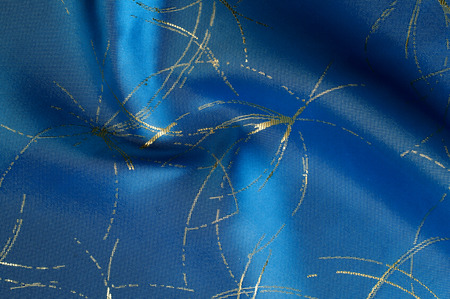 Texture, background, pattern. Blue silk fabric with painted sparks of fire. PURE SILK CREPE BACKED SATIN CHARMEUSE FABRIC