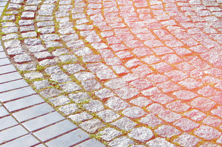 Texture, background, pattern. Granite covering. The texture of the stone pavement. Granite paved with cobblestone. Abstract background of old cobblestone close-up. Stock Photo