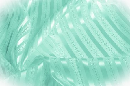 Background texture, pattern. Green silk fabric with a light stripe. Green cloth. Smooth elegant green satin background.