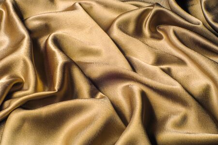 生地はシルク生地金属糸の金属光沢ゴールドに成っています。見事な滝を見ているようなだけシルクに位置するゴールデン イエローのシャルムーズ生地は単独で立っています。明るく光の流れの鋼鉄金属色 写真素材 - 90188673