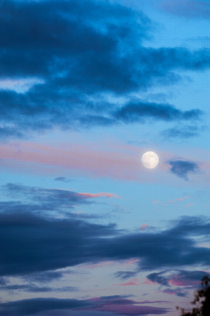 Evening landscape at sunset. The sky with the full moon. Severe storm clouds with pastel tones.