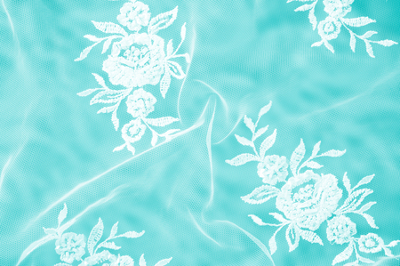 Texture, background, pattern. Lacy white fabric. Flowers made of lace fabric. Blue background of silk fabric. greeting card. Wallpaper for your desktop. Screensaver backdrop for designer Stock Photo