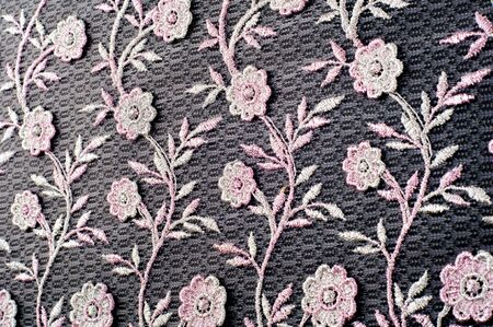 Texture, background, pattern. Pink lace decorated with flowers on a black background. Lace decorated with a pattern and decorative rose on a black background. Stockfoto