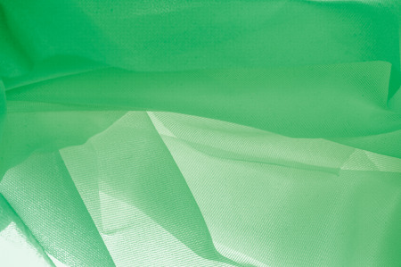 Texture, background, pattern. The texture of the silk fabric is green. Silk fabric is transparent. Fabric or liquid wave illustration of wavy creases of silk satin texture or velvet material