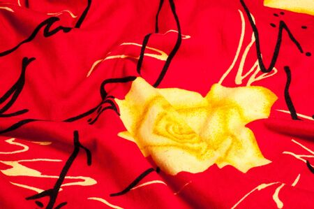 Background texture, pattern. Red silk fabric Yellow roses. Printed Chiffon Floral fabric Polyester Chiffon by the yard. Soft, translucent, light, fabric. Perfect for ball gown, wedding dress. Stock Photo