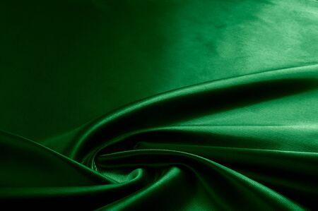 Texture, background, pattern. Texture of green silk fabric. Beautiful emerald green soft silk fabric.