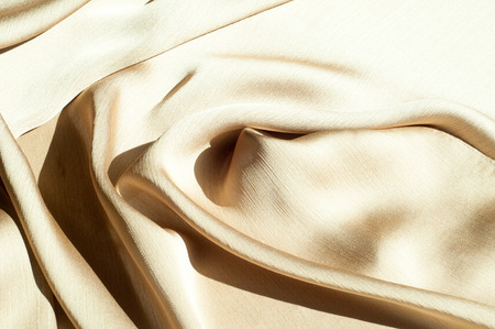 Texture, background, pattern. Womens shawl Colors. Goldenrod. Lemon cream. The Navajo is white. The old gold. silk fabric. Stock Photo