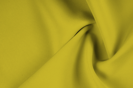 texture, pattern. Mustard silk fabric. Deep tone for autumn and winter, add this silk chiffon for your design. Light and airy, use its uplifting drapery to create easily flowing pieces. Stock Photo
