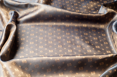 Texture background pattern. Brown silk fabric. Abstract background of luxury fabrics or liquid waves or wavy creases. Smooth elegant golden silk or satin In Sepia toned. Retro style