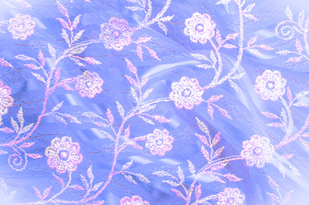 Texture, background, pattern. Pink lace decorated with flowers on a blue background. Background of pink, blue, beautifully decorated with flowers. pattern with pink lace on the blue background