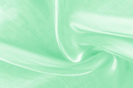Background texture, pattern. Green silk background with some soft folds and highlights. green background abstract cloth or liquid wave illustration of wavy folds of silk texture satin