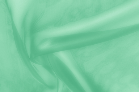 Texture, background, pattern. Pale green silk fabric. It is very soft and thin tulle, soft silk tulle. Looks like a drapery, much softer than a wedding illusion Stock Photo
