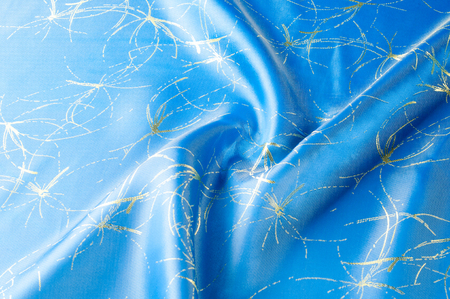 Background texture, pattern. Fabric blue silk with gold pattern. Created in the Renaissance style, the image of fruit twists around each other with golden branches on soft luminous silk. Stock Photo
