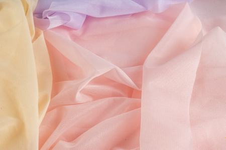 Texture, background, pattern. Silk transparent fabric. Blue yellow pink shades. of a color intermediate between red and white, as of coral or salmon.