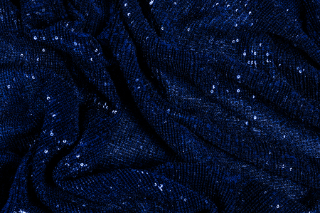 blue fabric with paillettes. For a glamorous affair, sport this blue mask. The coverage of the solid mesh strength remains a dense arrangement of circular childrens sparkles for the entire coating Stock Photo