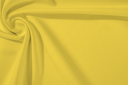 Texture Background. Template. Cloth - silk yellow. This yellow creme silk crepe de сhina shows a simple elegance. The creamy tone of ivory is textured with wrinkle waves, as it can boast a subtle sheen