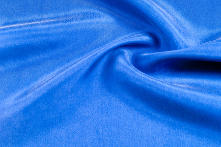 Background texture, pattern. Thick thick silk fabric of blue color. Add a touch of luxury to any design, building it with this super-heavy and very dense polyester fabric.