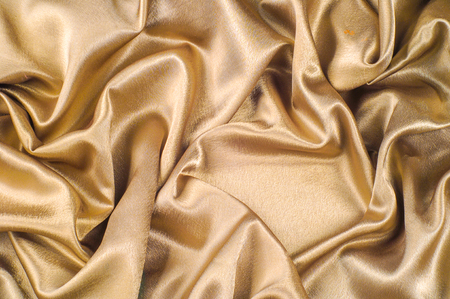 Fabric made of silk fabric metal thread metallic sheen gold. Just like looking at a stunning waterfall, this golden yellow Silk Charmeuse stands alone. Luminous and light-flowing steel metallic color Stok Fotoğraf