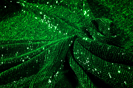 Texture, background, pattern, green fabric with paillettes. Make a statement with sequins Sequins on this fabric are sewn into overlapping straight lines that grab your eye from any angle.