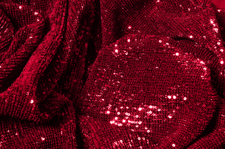 Texture, background, pattern, red fabric with paillettes. Look at these neon red sequins. Round neon pink sparkles glitter overlapping iridescent glitter on a clean purple grid.