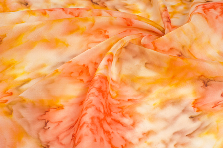 Texture, background, pattern. Silk fabric with a blurry red yellow pattern. Yellow, red and cream flowers on white