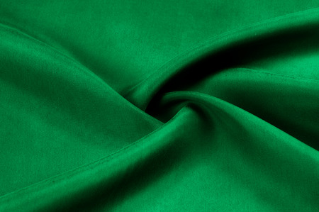 Background texture, pattern. Thick thick silk fabric is green. This satin fabric is ideal for creating a smooth flow in design, it has a liquid drape and exquisite shine.