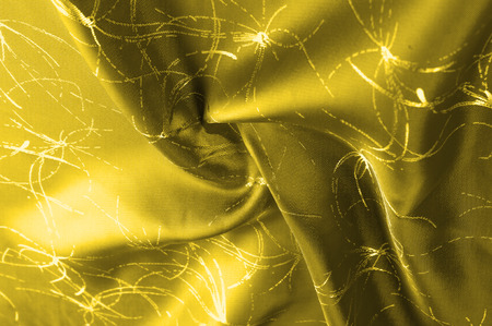texture Silk fabric Golden yellow with a pattern. Add an unexpected shine of sophistication when introducing this mustard velvet. Soft light velvet depicts a playfully twirled design in decadent gold. Stock Photo