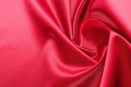 Texture, background, pattern. Red silk fabric.This satin fabric is perfect for making fabric flowers for use in hair accessories, jewery making, and fabric bouquets.  Archivio Fotografico