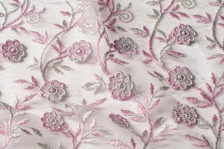 Texture, background, pattern. Pink lace decorated with flowers on a white background. Background of pink lace fabric beautifully decorated with flowers Stock Photo
