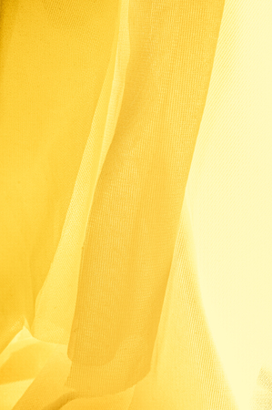 Texture, background, pattern. The texture of the silk fabric is yellow. Silk fabric is transparent. Stock Photo
