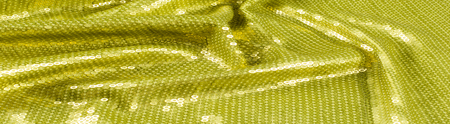 Fabric texture with green sequins. a small, shiny disk sewn as one of many onto clothing for decoration Stock Photo