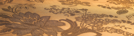 Fabric silk texture color Sandy Brown. With woven into the fabric flowers