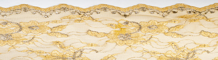 Texture. Lace fabric golden yellow color photos made in the studio. a fine open fabric, typically one of cotton or silk, made by looping, twisting, or knitting thread in patterns and used especially for trimming garments.