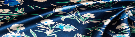 Fabric silk texture blue, flowers, abstract. a fine, strong, soft, lustrous fiber produced by silkworms in making cocoons and collected to make thread and fabric.