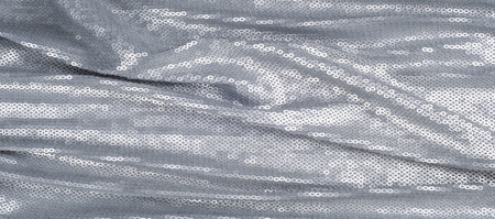 Silk fabric texture, background. Covered with sequins, silver color Фото со стока