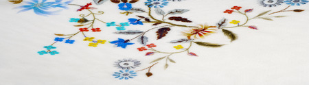 texture, background, fabric cotton white. With flowers stylized embroidery. a soft white fibrous substance that surrounds the seeds of a tropical and subtropical plant