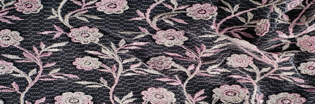 Texture, background, pattern. Pink lace decorated with flowers on a black background. Lace decorated with a pattern and decorative rose on a black background. Stock Photo