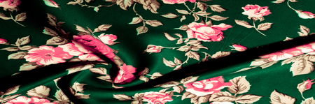 Background, texture, pattern. green fabric with painted rose flowers, Fine and gentle to the touch silk with a noble weave, Printed in elegant and delicate roses in bright shades of pink and amaranth Stock Photo