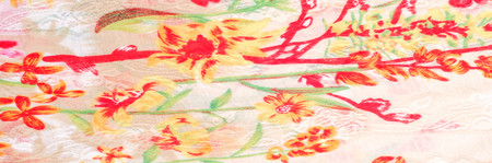 Texture, background, pattern. Silk dress. Bright red green flowers on a white background. Abstract pattern